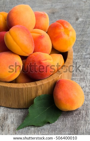 Apricots with leaves on the old wooden table #506400010
