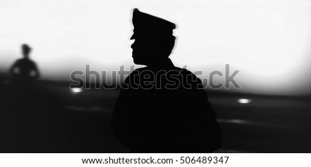 Black silhouette on wall background of a uniformed police officer, Style photo blur
