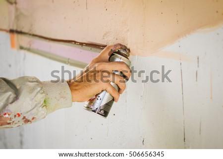 Graffiti artist painting with aerosol spray on the wall #506656345