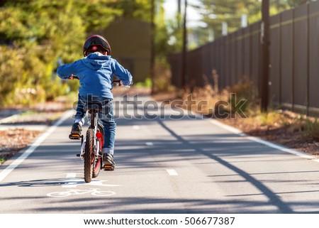 Australian boy riding his bicycle on bike lane on a day, South Australia Royalty-Free Stock Photo #506677387