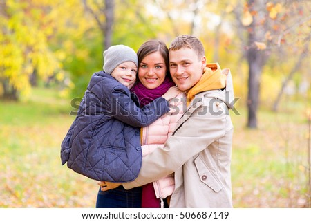 Father and Mother With Young Son On hands Autumn Park walks between trees, smiling together #506687149