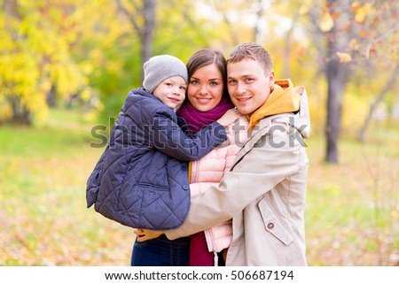 Father and Mother With Young Son On hands Autumn Park walks between trees, smiling together #506687194
