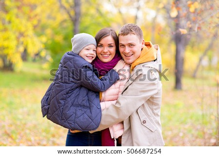Father and Mother With Young Son On hands Autumn Park walks between trees, smiling together #506687254