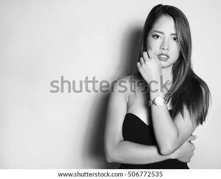 beautiful young asian woman with long hair posing in casual clothes and wearing a wrist watch #506772535