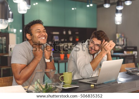 Look at this one. Happy smiling two guys enjoying while sitting in cafe and using digital gadgets #506835352