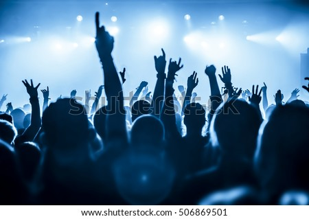 silhouettes of concert crowd in front of bright stage lights #506869501