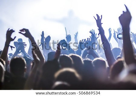 silhouettes of concert crowd in front of bright stage lights #506869534