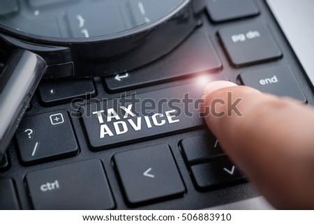 Finger on laptop keyboard written Tax Advice #506883910