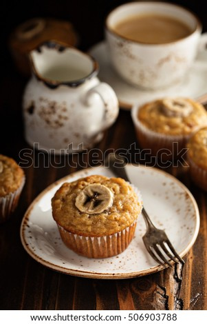 Healthy banana muffins with slices on top with coffee in dark rustic setting #506903788