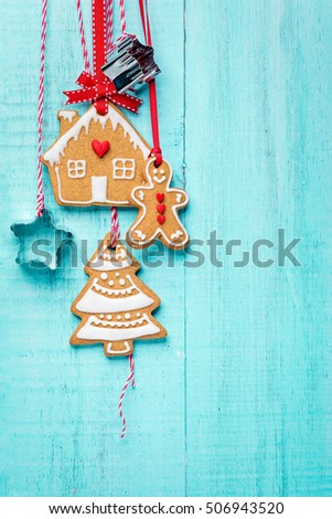 Gingerbread Man, house and tree cookies hanging with ribbon over a blue background