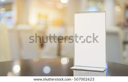 Mock up Menu frame  in Bar restaurant ,Stand for booklets with white sheets of paper acrylic tent card on wooden table on cafeteria  blurred background