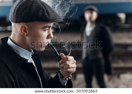 brutal gangsters smoking and posing on background of railway. england in 1920s theme. fashionable confident man. atmospheric moments. space for text #507092863
