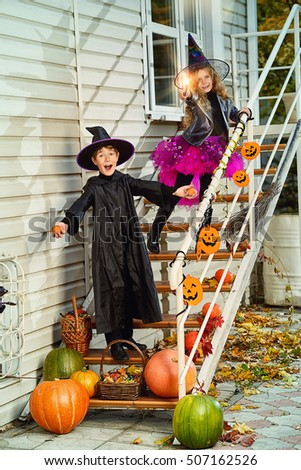 Happy children in a costumes of witches and wizards celebrating halloween. Trick or treat. Halloween party. #507162526