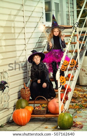 Happy children in a costumes of witches and wizards celebrating halloween. Trick or treat. Halloween party. #507162640