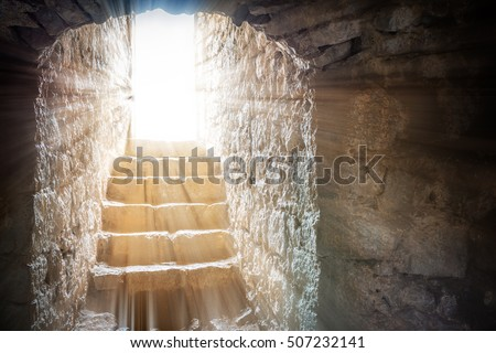 Resurrection of Jesus Christ. Religious Easter background, with strong light rays shining through the entrance into the empty stone tomb. Artistic strong vignette, contrast, dramatic dark-light edit. Royalty-Free Stock Photo #507232141