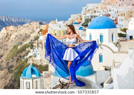 Woman in beautiful dress with blue train stands on the roof of the architecture of Santorini #507335857