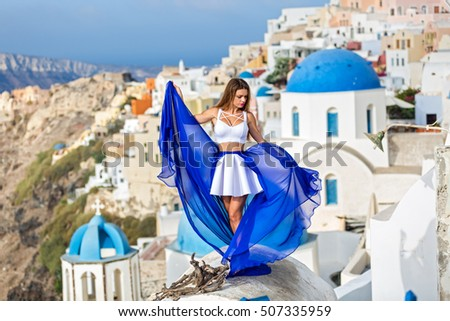Woman in beautiful dress with blue train stands on the roof of the architecture of Santorini #507335959