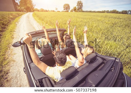 Group of best friends having fun at car trip - Four caucasian people with arms up in a convertible car, view from above #507337198