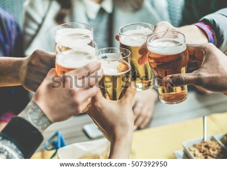 Multiracial group of friends enjoying a beer - Young people hands toasting and cheering aperitif beers half pint - Friendship and youth concept - Warm vintage raw filter - Focus on bottom hand Royalty-Free Stock Photo #507392950