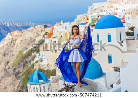 Woman in beautiful dress with blue train stands on the roof of the architecture of Santorini #507474211