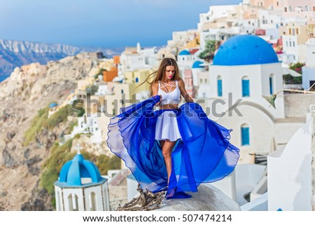 Woman in beautiful dress with blue train stands on the roof of the architecture of Santorini #507474214