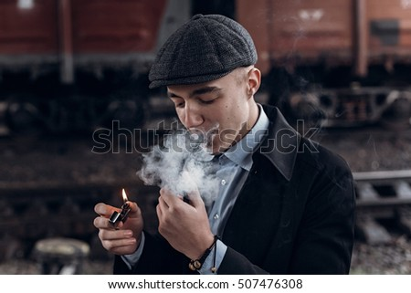 sherlock holmes look, man in retro outfit, smoking wooden pipe. england in 1920s theme. fashionable confident gangster. atmospheric moments. space for text #507476308