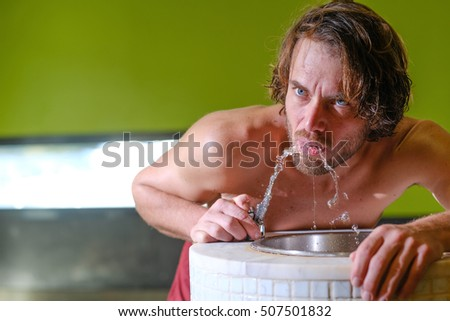 Beautiful man with blue eyes drinking water from a water fountain in a sauna  #507501832