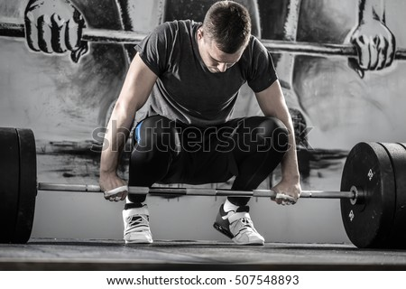 Powerful guy with a beard prepares to raise up a barbell in the squat in the gym on the wall with picture background. He wears sportswear with the white sneakers. Man looks at the barbell. Horizontal.