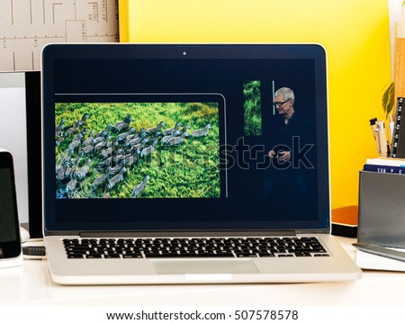 PARIS, FRANCE - OCT 28 2016: Apple Computers website on new MacBook Pro Retina with OLED Touch bar in geek creative room Keynote Tim Cook talking about the MacBook Pro and its advantages #507578578