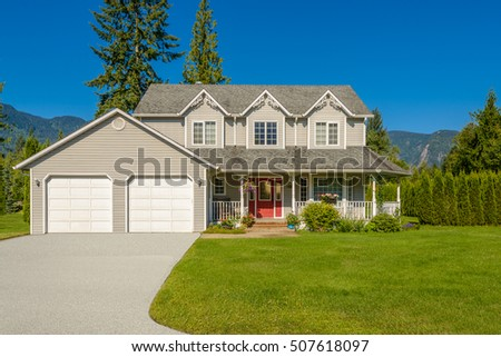 Custom built luxury house with nicely trimmed and landscaped front yard, lawn in a residential neighborhood. Vancouver Canada. #507618097