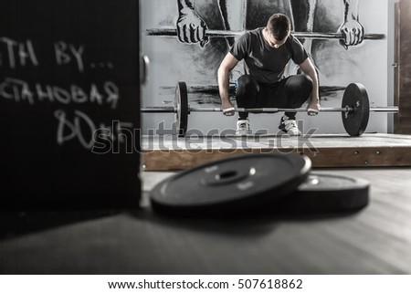 Sportsman prepares to raise up a barbell in the squat in the gym on the wall with picture background. He wears sportswear with the white sneakers. Man looks at the barbell. Horizontal.