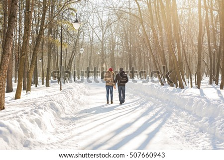 happy couple walking through a snowy forest in winter #507660943