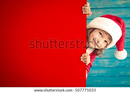 Child holding empty banner. Kid hiding behind card blank. Christmas Xmas winter holiday concept