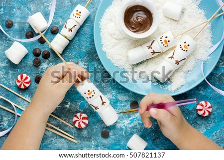 Child making snowman marshmallow pops, kitchen composition for winter holiday. Funny food art idea for Christmas dessert treat top view #507821137
