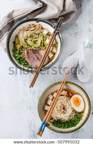 Two bowl of different asian style soups with green tea soba noodles, egg, mushrooms, beef, onion and tofu cheese, served with chopsticks and spoon over white wooden background. Top view #507995032