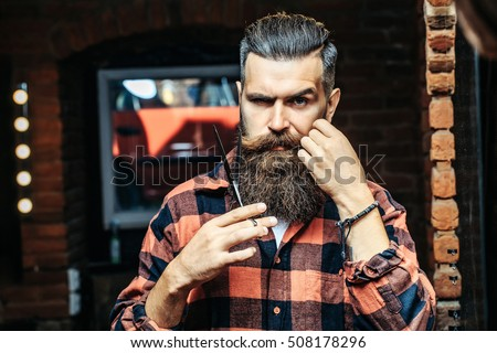 Handsome bearded man hipster with stylish haircut and beard holding scissors in red checkered shirt near mirror with serious face in beauty salon or barbershop as barber near brick wall #508178296