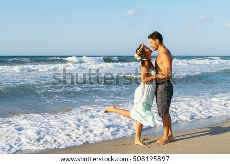 Loving young couple having fun kissing at the beach in summer at dusk. Barefoot wearing turquoise dress and shorts, enjoying getting wet splashing in the ocean water. Holiday background travel concept #508195897