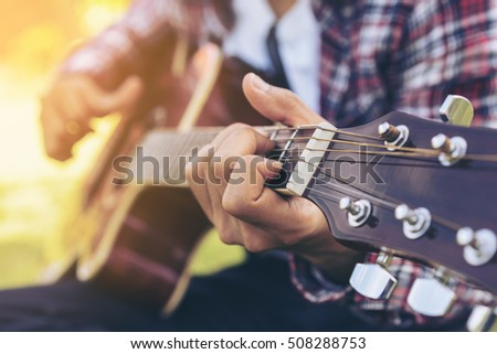 Man 's hand playing acoustic guitar, folk song. Nature background. #508288753