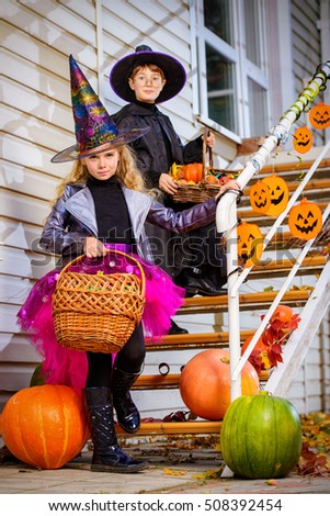 Happy children in a costumes of witches and wizards celebrating halloween. Trick or treat. Halloween party. #508392454