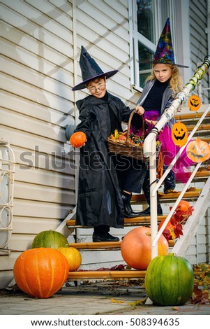 Happy children in a costumes of witches and wizards celebrating halloween. Trick or treat. Halloween party. #508394635