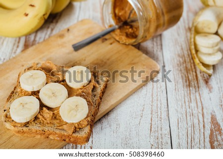 Homemade peanut butter and banana sandwich on wooden background #508398460