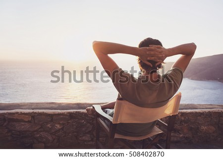 Enjoying life. Back side of young man looking at the sea, vacations lifestyle concept Royalty-Free Stock Photo #508402870