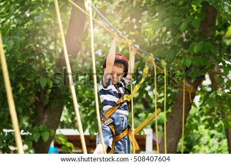 Boy enjoys climbing in the ropes course adventure. #508407604