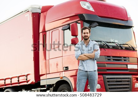 handsome masculine truck driver standing outside with his vehicle behind with folded arms #508483729
