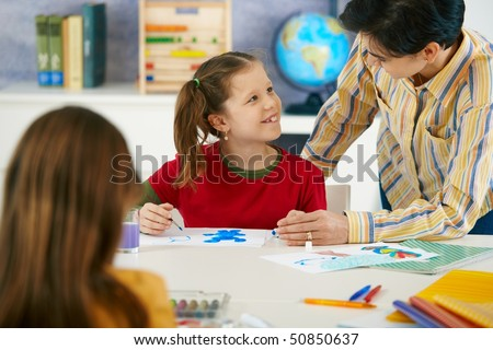 Teacher teaching painting to elementary age children in classroom at primary school. #50850637