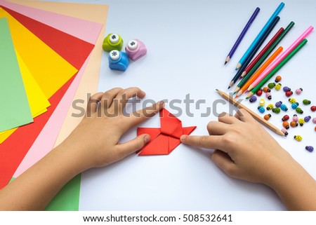 Children's hands do origami  bird from red paper. Working place is decorated with leaves of color paper, scissors, colored wood ladybugs and pencils. #508532641