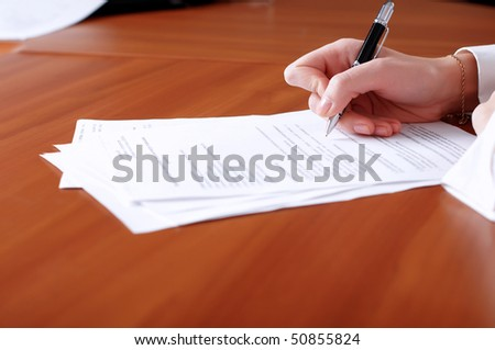 person's hand signing an important document #50855824