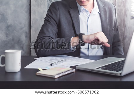 Close up of Businessman working on the desk and checking time on his wrist watch. #508571902