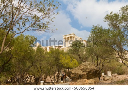 The Acropolis of Athens in Greece behind olive trees as a pigeon flies by #508658854