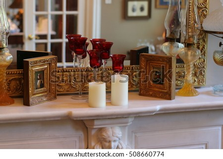 Mantel with mirror, candles, and paintings